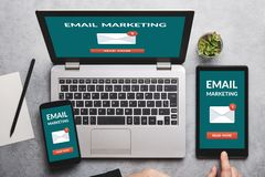 Email marketing concept on laptop, tablet and smartphone screen. Over gray table. All screen content is designed by me. Flat lay stock photos