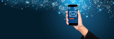 Email marketing and newsletter concept. Sending a message on smartphone screen in businesswoman hand.  stock image