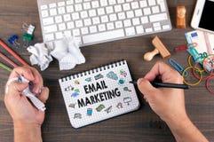 Email marknadsföringsbegreppsidékläckning vid kontorsskrivbordet med brevpapper arkivfoto