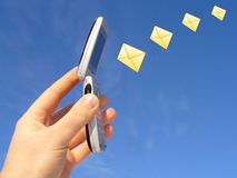 Email Messages on Cellphone. A hand holds an open cellphone to the clear blue sky or background with four small yellow envelopes fly through the air as if coming Stock Images