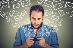 Email upptagna överförande meddelandeemails för chockad man från den smarta telefonen att flyga för symboler av mobiltelefonen arkivfoto