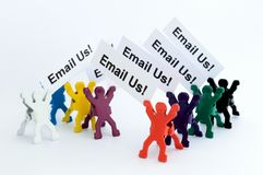 Email Us coloured figures. Small figures holding email us text Stock Photo