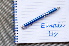 Email us write on notebook. Email us text concept write on notebook royalty free stock photo