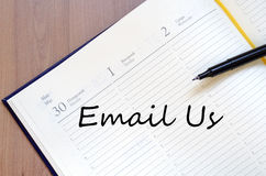 Email us write on notebook. Email us text concept write on notebook royalty free stock images