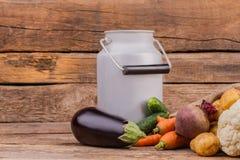 Emaillierte Milch kann mit Griff und rohem Frischgemüse stockbild