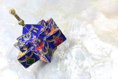 Emailliertes blaues sternförmiges Chanukka-dreidel auf einem weichen weißen Hintergrund Lizenzfreies Stockfoto