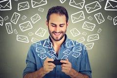 Emails de envoi occupés de messages de jeune homme heureux de portrait de téléphone intelligent Photo libre de droits