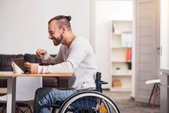Emails handicapés de sourire de lecture de type pendant le petit déjeuner Image stock