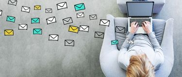Emails with man using a laptop. In a modern gray chair stock images