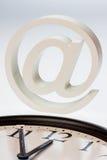 Emailtecken och klocka Arkivfoto