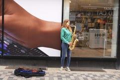 EMALE音乐家在街道招待 免版税库存图片