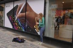 EMALE音乐家在街道招待 库存照片