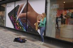 EMALE音乐家在街道招待 库存图片