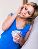 Emale with antibiotic and glass of water indoors. Blonde american female with antibiotic and glass of water indoors Royalty Free Stock Image