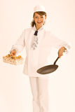 Emale chef with chanterelles and pan. Female chef with a basket full of mushrooms and pan Royalty Free Stock Image