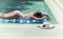 Emale en un traje de baño que miente cerca de la piscina Imagen de archivo