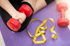 Emale hand lifting dumbbell from fitness mat next to measuring t. Closeup photo of female hand lifting dumbbell from fitness mat next to measuring tape Stock Photos