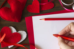 Emale hand writes a note on Valentine`s Day Royalty Free Stock Image