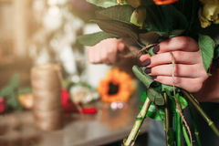 Emale hands with bouquet of flowers closeup. Female hands with bouquet of flowers closeup against blur background Royalty Free Stock Photo