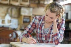 Emale-Lehrling, der Kenntnisse in der Werkstatt nimmt stockfotos