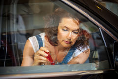 Emale mechanic repairing a car door with a screwdriver. Portrait of a beautiful female mechanic repairing a car door with a screwdriver Stock Images