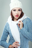 Emale model wearing a blue woolen sweater. Beautiful smiling mixed rase caucasian/asian female model wearing a blue woolen sweater, a scarf, a knitted cap Stock Photo