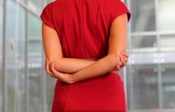 Emale no vestido vermelho que estica os braços imagem de stock royalty free