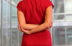 Emale in red dress stretching arms. White female in red dress stretching arms on her back, close up Royalty Free Stock Image