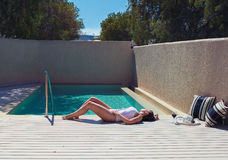 Emale in a swimsuit lying near the pool. Female in a swimsuit lying near the pool with hat and wine Stock Photos