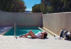 Emale in a swimsuit lying near the pool. Female in a swimsuit lying near the pool with hat and wine Royalty Free Stock Photos