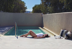 Emale in a swimsuit lying near the pool. Female in a swimsuit lying near the pool with hat and wine Royalty Free Stock Photography