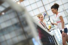 Emale tennisspelare som skakar händer över netto Royaltyfri Bild