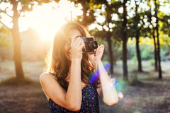 Emale with vintage camera in park. Young caucasian female with vintage camera in park Stock Image