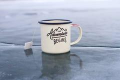 Emaliujący kubek z gorącą herbatą i etykietką z pustą przestrzenią dla inskrypci od herbacianej torby na błękitnym jasnym lodzie  Fotografia Stock