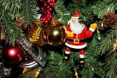 Emalj Santa Claus och andra prydnader på den traditionella julgranen Royaltyfri Bild