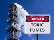 Emanações tóxicas do perigo do sinal e a chaminé da fábrica com fumo no céu fotografia de stock