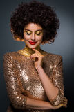 Emanating gloss. Of shiny and golden clothes with special elements on lady's body and face. Sexy diva looks down. Neutral grey background. Pleasant smile Royalty Free Stock Photos