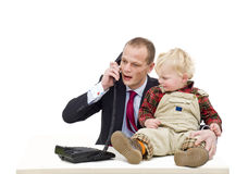Emancipation. A working father on the phone, whilst caring for his toddler boy, a conceptual image for the contemporary emancipation, where fathers are taking stock images