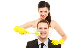 Emancipation idea concept. Humorous funny wedding couple bride and groom. Woman brushing teeth of her men showing her domination and taking control. Isolated stock photography