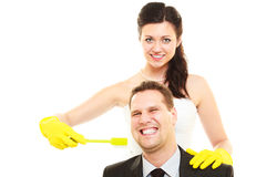 Emancipation idea concept. Humorous funny wedding couple bride and groom. Woman brushing teeth of her men showing her domination and taking control. Isolated royalty free stock photography