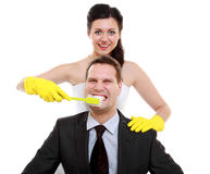 Emancipation idea. Woman brushing teeth of her man, humor. Emancipation idea concept. Humorous funny wedding couple bride and groom - women brushing teeth of her stock photos
