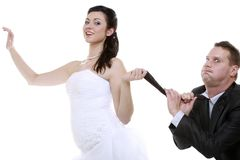 Emancipation idea. Woman pulling on mans tie, funny couple. Emancipation idea concept. Humorous funny wedding couple bride and groom - women pulling the tie of a stock photo