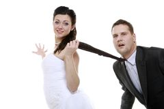 Emancipation idea. Woman pulling on mans tie, funny couple. Emancipation idea concept. Humorous funny wedding couple bride and groom - women pulling the tie of a stock photography