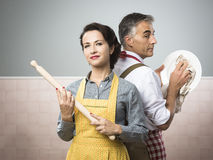 Emancipation. Smiling strong women with rolling pin watching her husband cleaning dishes royalty free stock photography