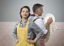 Emancipation. Smiling strong women watching her husband in apron cleaning dishes royalty free stock photography