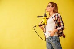 Emancypacyjna kobieta zręcznie trzyma świder, stoi między pudełkami studio obrazy stock