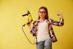 Emancypacyjna kobieta zręcznie trzyma świder, stoi między pudełkami studio zdjęcie stock