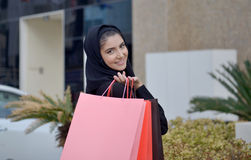 Emarati Arab woman coming out of shopping Royalty Free Stock Images