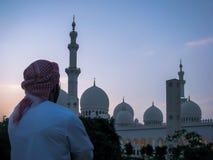 Emarati mężczyzna patrzeje Sheikh Zayed Uroczystego meczet fotografia stock