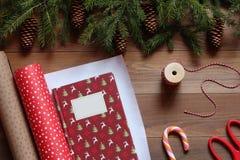 Embalagem do livro de Natal no papel do presente em uma tabela de madeira Fotos de Stock